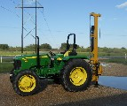 The Model 40 fence post driver shown on a mid-size John Deere tractor.