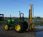 Anothe view of the Model 40 fence post driver shown on a mid-size John Deere tractor.