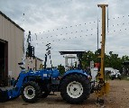 The Model 40 fence post driver on a New Holland Tractor.
